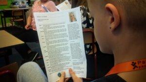 jongen leest informatiefolder over edelstenen