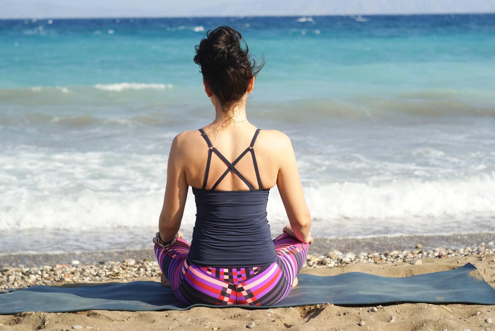 vrouw mediterend aan zee