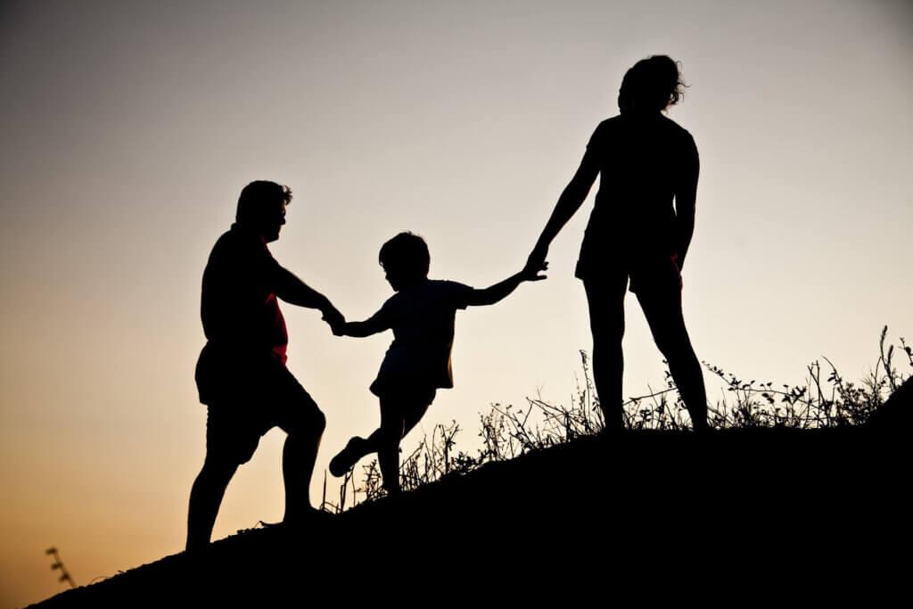 Familieopstellingen. Silouet van Ouders en jong kind hand in hand de helling op.