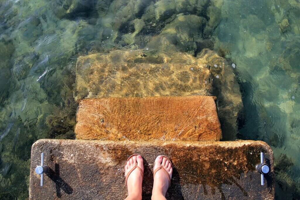 Ga je het doen? Voeten aan de rand van water.